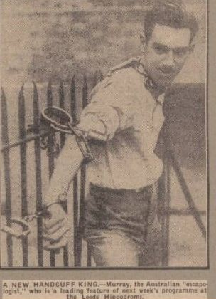 Murray the Escapologist handcuffed to railings