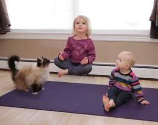 Little girl levitating above a yoga mat
