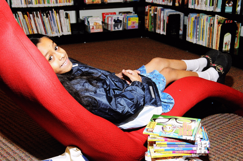 Child seated in library