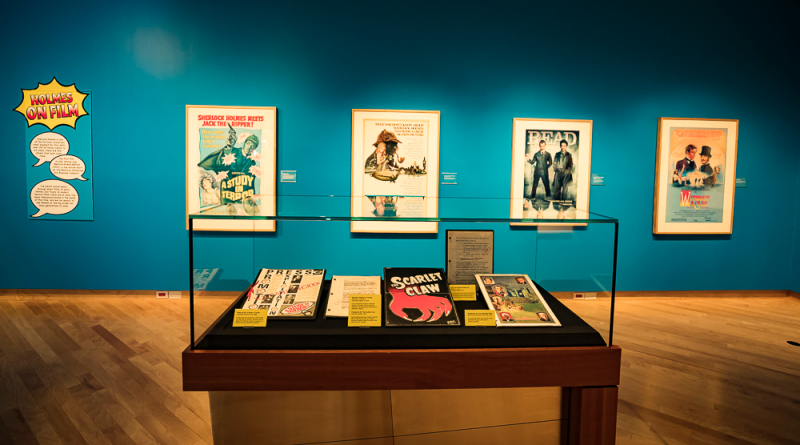 A glass display case with scripts and other film epherma. A series of film posters are visible framed on the wall.