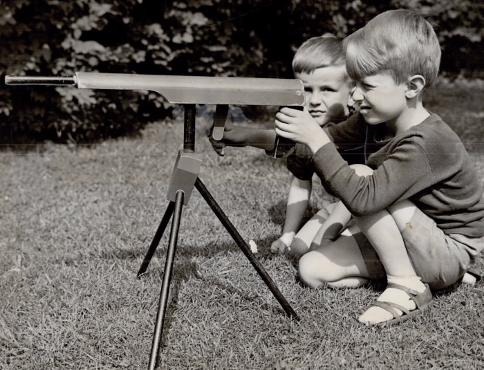 Two boys playing with a toy machine-gun