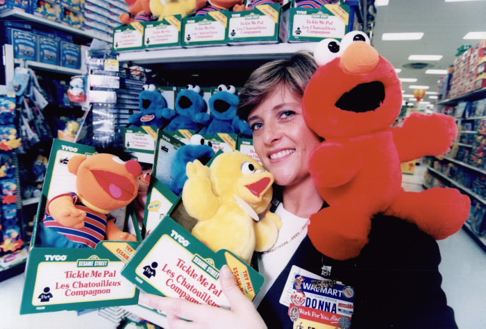 Inside a toy store a woman carries three stuffed animal toys