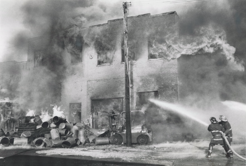 Two fire fighters spray into a burning building