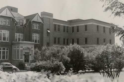 Large brick building with trees in front