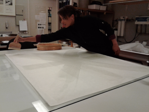 Large white paper and a woman applying substance with a tool in a conservation lab